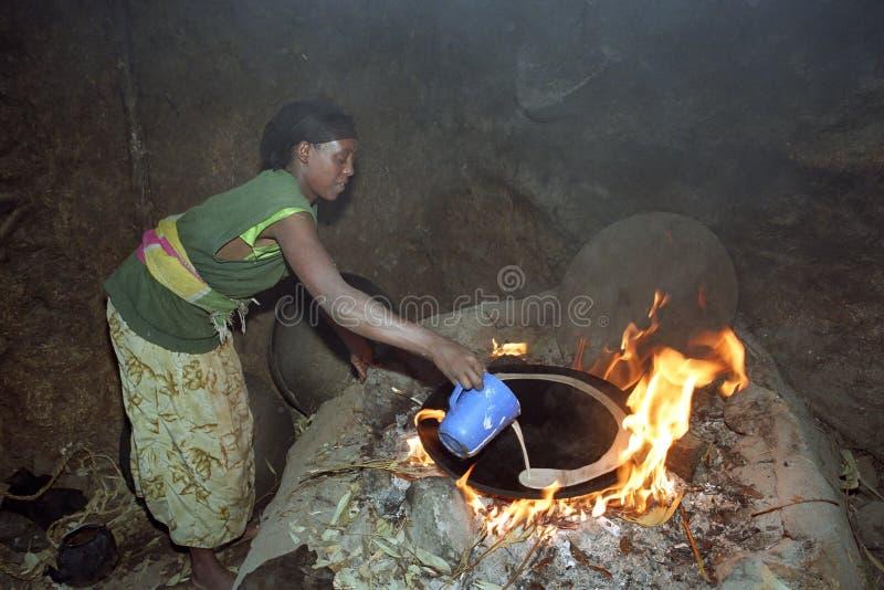 La donna etiopica cuoce il injera su fuoco di legno fotografia stock
