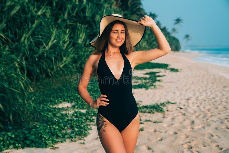 La donna europea allegra radiante bella porta un costume da bagno alla moda, un cappello alla moda, la chiude occhi con piacere immagine stock libera da diritti