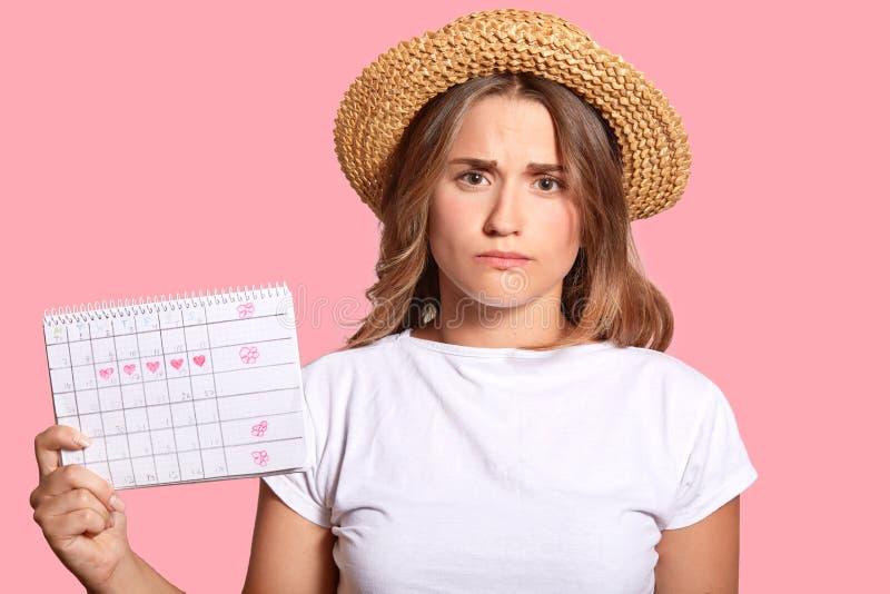 La donna europea dispiaciuta in cappello di paglia e maglietta casuale, tiene il calendario di mestruazione, porta la maglietta c fotografia stock