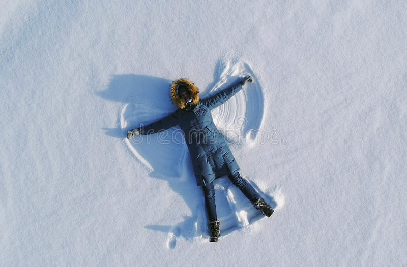 La donna fa l'angelo della neve che risiede nella neve Vista superiore Foto aereo immagini stock libere da diritti
