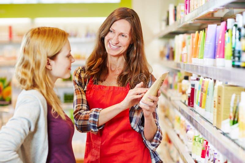 La donna in farmacia ottiene il consiglio dalla venditora immagine stock