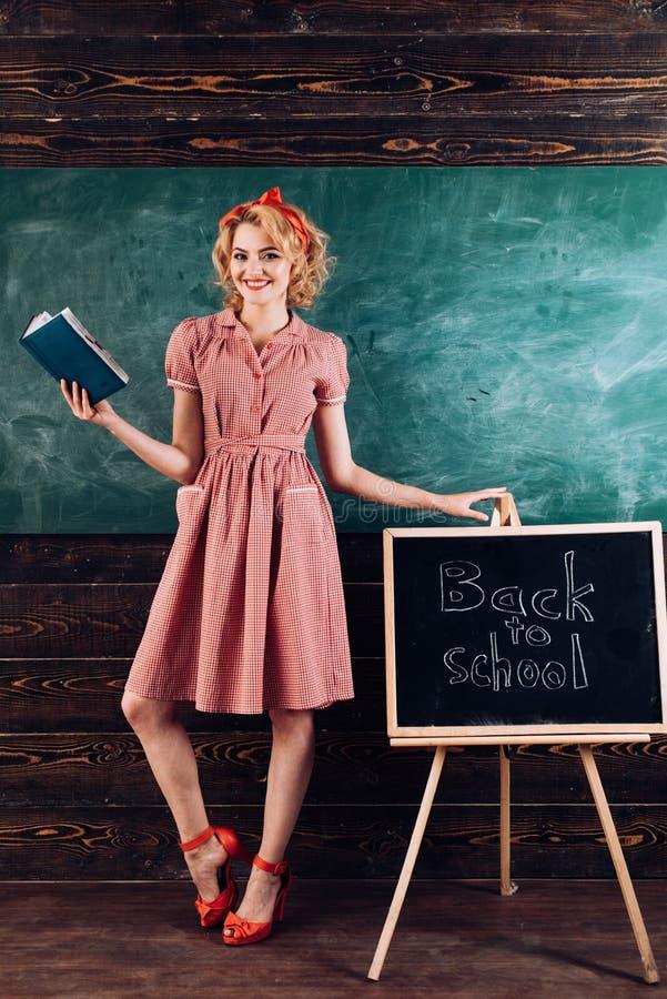 La donna felice è di nuovo alla scuola con il nuovo libro L'insegnante dell'inglese sorride con il libro alla lavagna dell'aula S fotografie stock libere da diritti