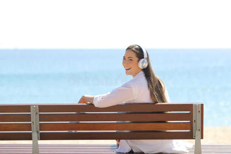 La donna felice che ascolta la musica sulla spiaggia vi esamina immagini stock