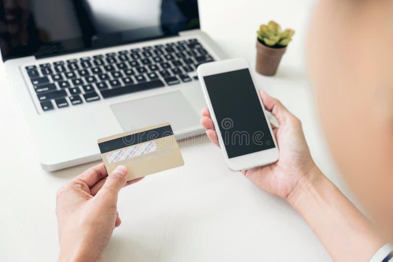 La donna felice che per mezzo dello Smart Phone e la carta di credito registrano i pagamenti fotografie stock libere da diritti