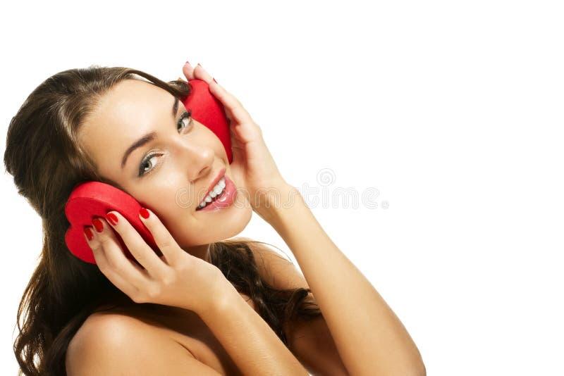 La donna felice che tiene il cuore rosso ha modellato la casella sul suo ea fotografia stock