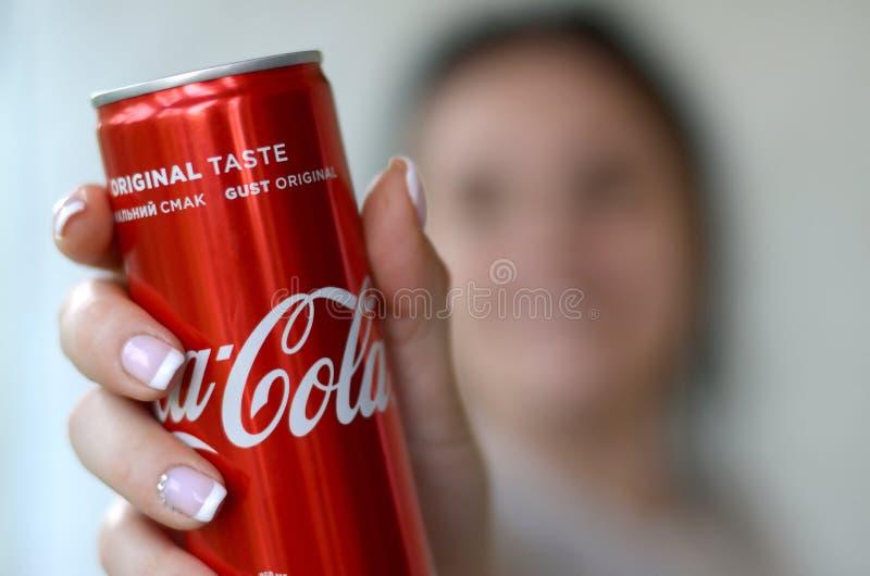 La donna felice che tiene latta di alluminio analcolica di Coca-Cola barattolo nell'interno del garage immagine stock libera da diritti