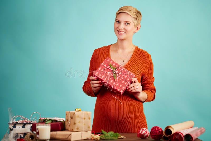La donna felice che tiene la scatola attuale rossa, aspetta per i saluti di Natale fotografie stock