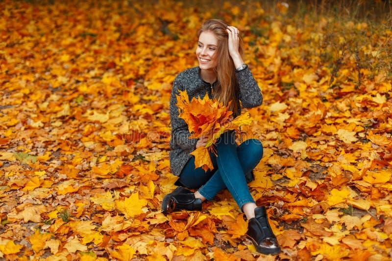 La donna felice con un sorriso in suo cappotto si siede in autunno giallo immagini stock