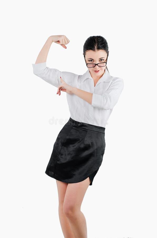 La donna felice di affari che flette il suo braccio muscles per mostrare come stong s fotografia stock