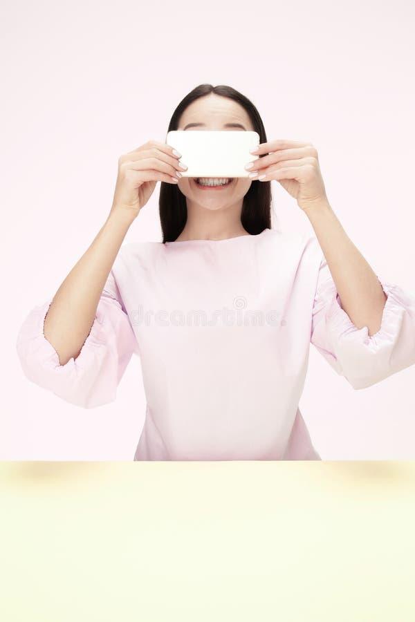 La donna felice di affari che si siede con il telefono cellulare contro il fondo rosa fotografie stock libere da diritti