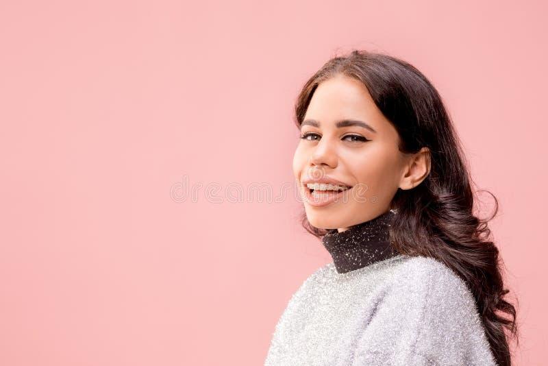 La donna felice di affari che sta e che sorride contro il fondo pastello fotografia stock
