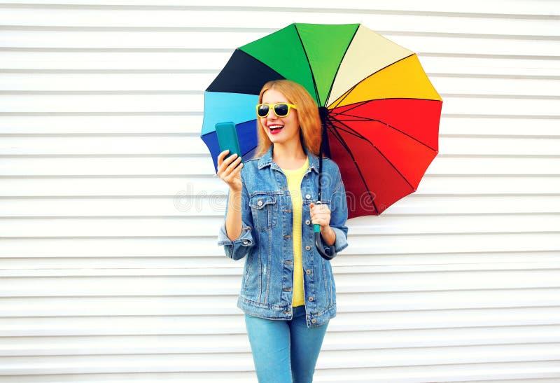 La donna felice di modo che ride con l'ombrello variopinto, tiene lo smartphone fotografia stock libera da diritti