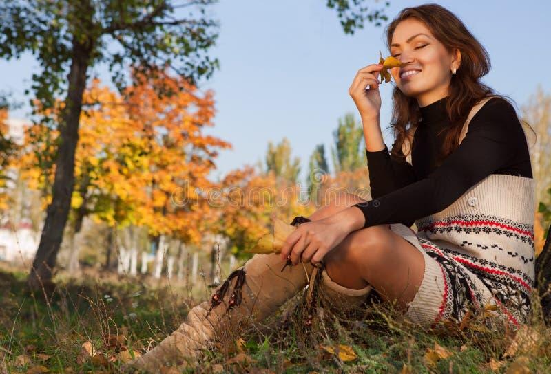 La donna felice gode dell'odore delle foglie gialle fotografie stock libere da diritti