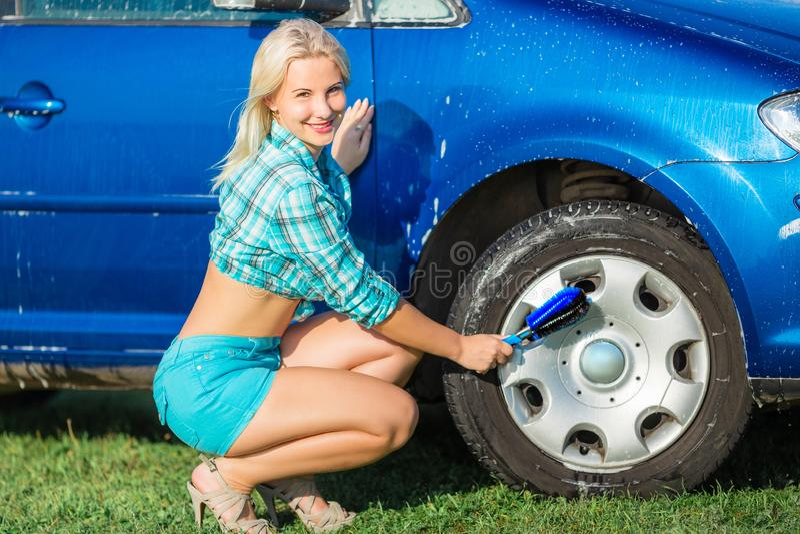 La donna felice lava l'automobile fotografia stock libera da diritti
