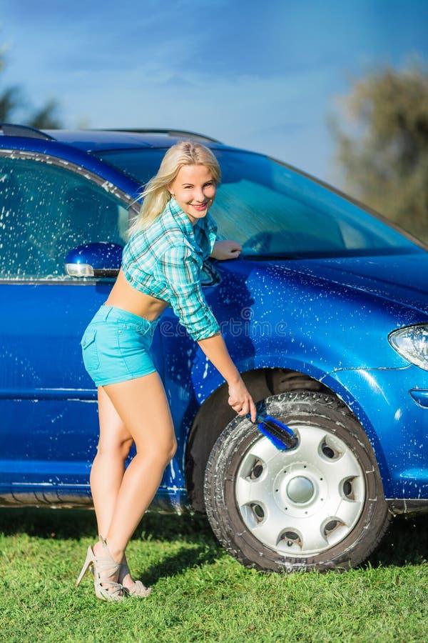 La donna felice lava l'automobile fotografia stock