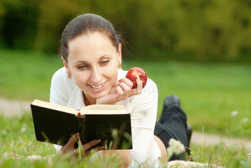 La donna felice legge il libro fotografia stock libera da diritti