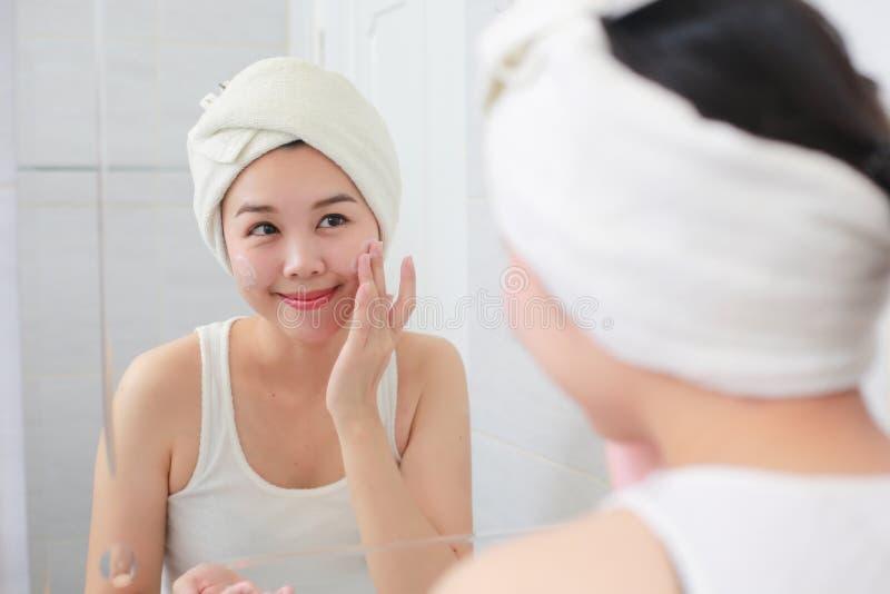 La donna felice pulisce la pelle con schiuma sul lavandino fotografia stock libera da diritti