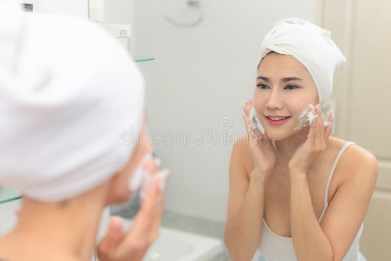 La donna felice pulisce la pelle con schiuma sul lavandino immagine stock libera da diritti