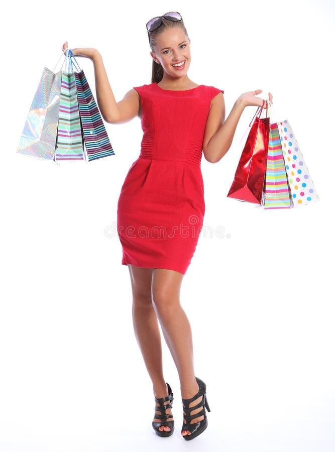 La donna felice sexy in regalo rosso di acquisto del vestito insacca immagini stock libere da diritti