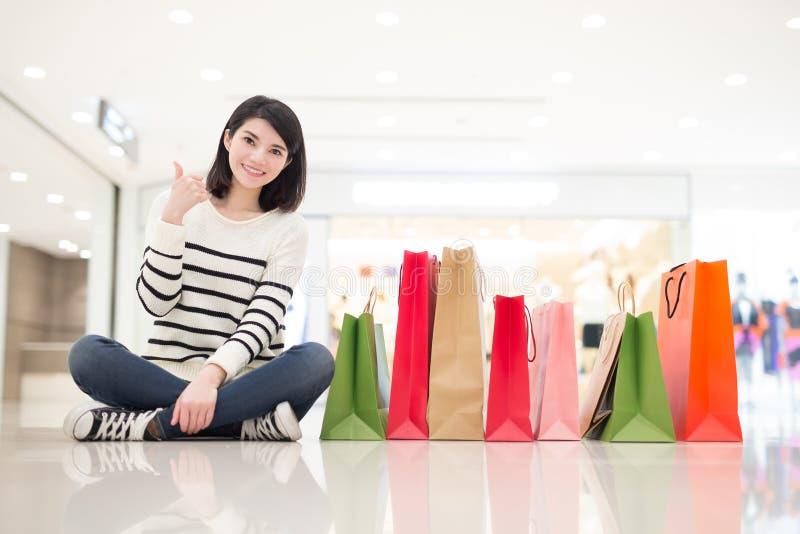 La donna felice si siede le borse di manifestazione immagini stock