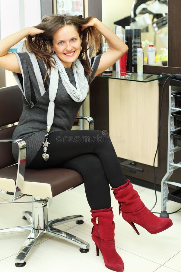 La donna felice si siede in poltrona e tocca i suoi capelli fotografia stock libera da diritti