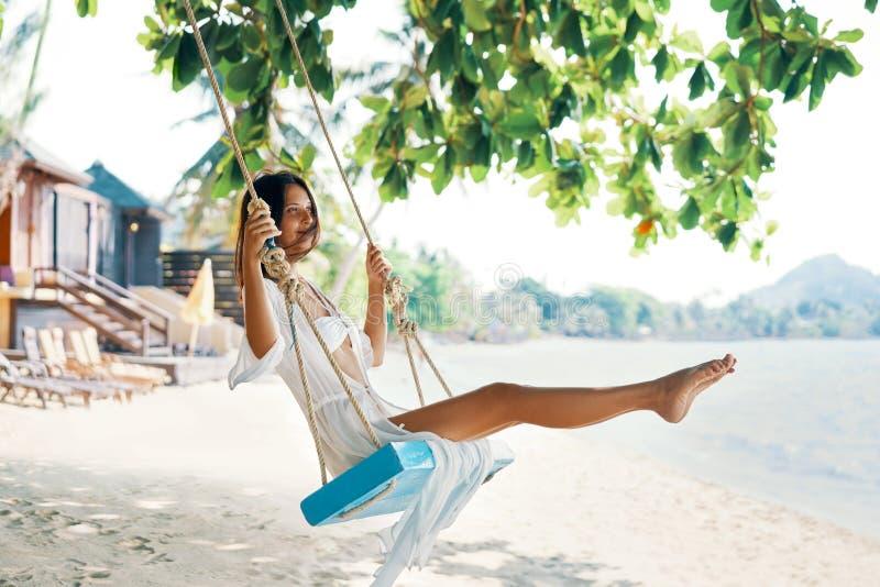 La donna felice spensierata su oscillazione sui bei paradiso tira fotografie stock