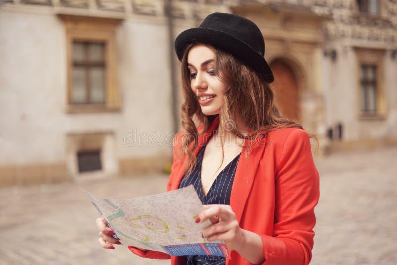 La donna felice sulla vacanza con la mappa, viaggiatore cammina la città Giorno pieno di sole Vista posteriore Una giovane donna  fotografia stock libera da diritti