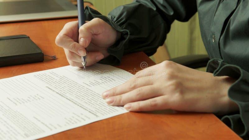 La donna firma un documento fotografie stock