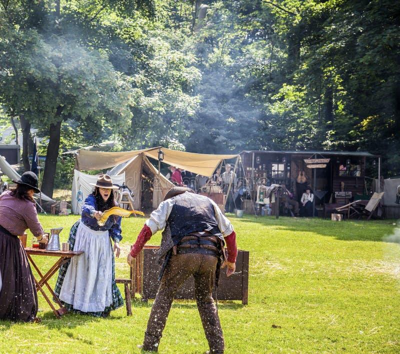 La donna getta la birra sopra il cowboy nella rimessa in vigore di scena di lotta immagine stock libera da diritti