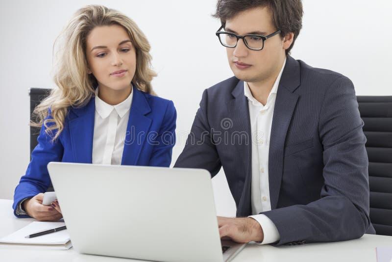 La donna in giacca sportiva blu e vetri d'uso di un tipo è nell'ufficio fotografia stock libera da diritti
