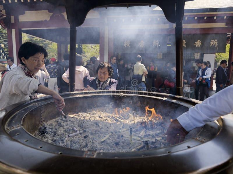 La donna giapponese accende il bastone di incenso nei grandi bruciaprofumi bronzei o il koro al tempio di Senso-ji fotografie stock