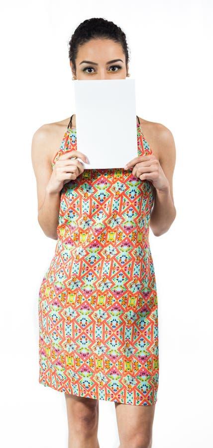La donna gioca con la carta in bianco e riguarda la parte del fronte Lei wea fotografie stock