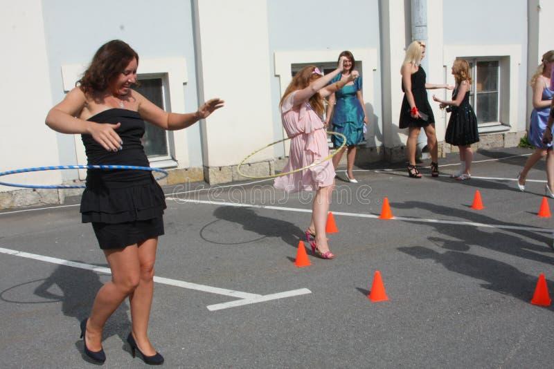 La donna gira il hula-hoop sul fondo della città della casa immagini stock