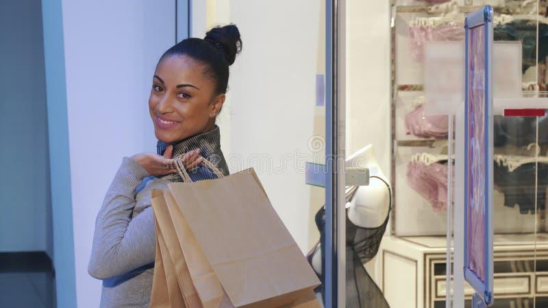La donna gira indietro vicino alla finestra di deposito con biancheria immagini stock libere da diritti