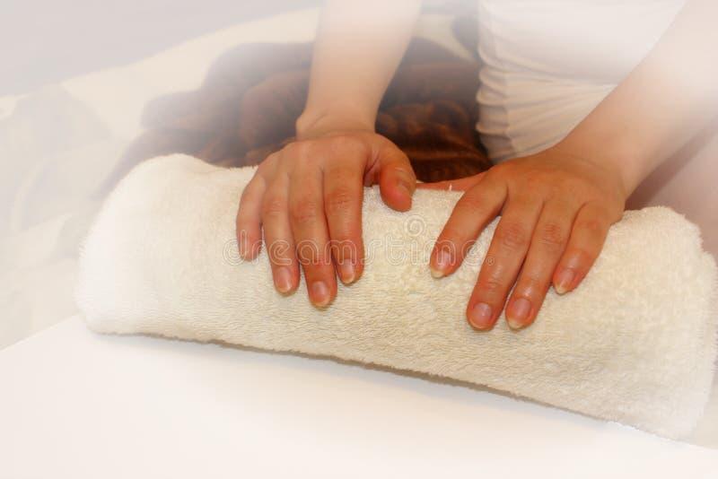 La donna giudica gli asciugamani puliti, la spazzola della mano e l'asciugamano, isolati su fondo bianco, per i trattamenti della immagine stock libera da diritti