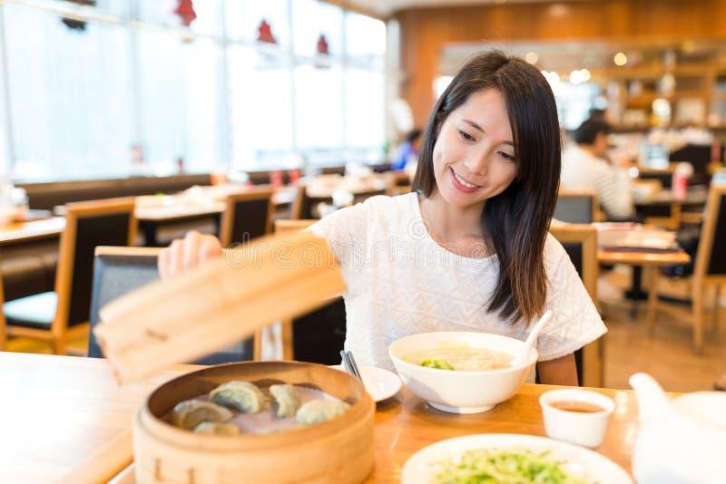 La donna gode del suo pasto in ristorante cinese immagine stock libera da diritti