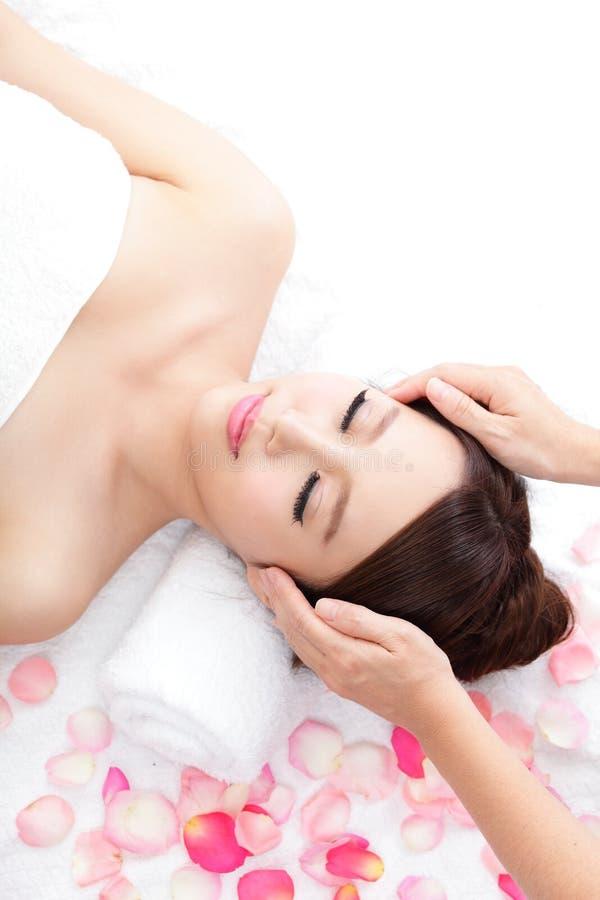 La donna gode di di ricevere il massaggio di fronte alla stazione termale con le rose fotografie stock