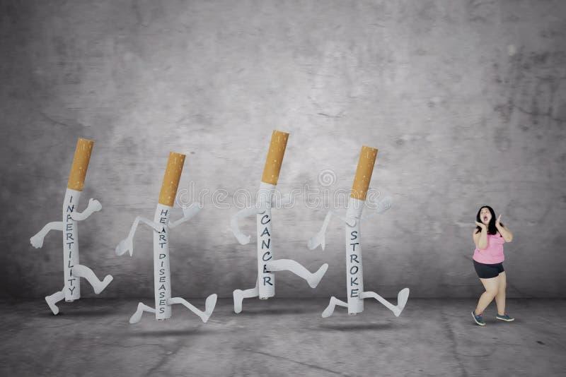 La donna grassa è inseguita dalle malattie sulle sigarette fotografia stock libera da diritti