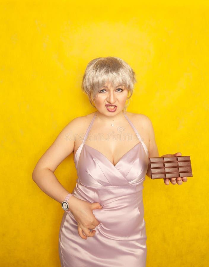 La donna grassottella sta con un fronte infelice e una barra di cioccolato in sua mano e tocca il grasso sulla sua pancia paffuta fotografia stock