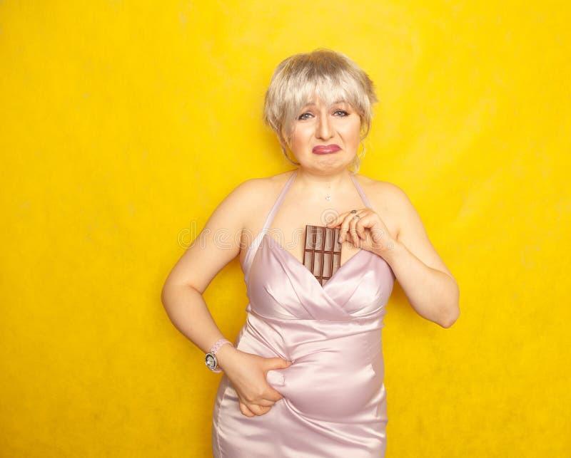 La donna grassottella sta con un fronte infelice e una barra di cioccolato in sua mano e tocca il grasso sulla sua pancia paffuta fotografia stock libera da diritti