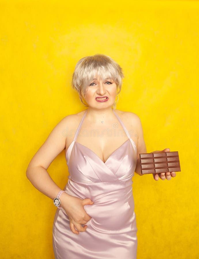 La donna grassottella sta con un fronte infelice e una barra di cioccolato in sua mano e tocca il grasso sulla sua pancia paffuta fotografie stock libere da diritti
