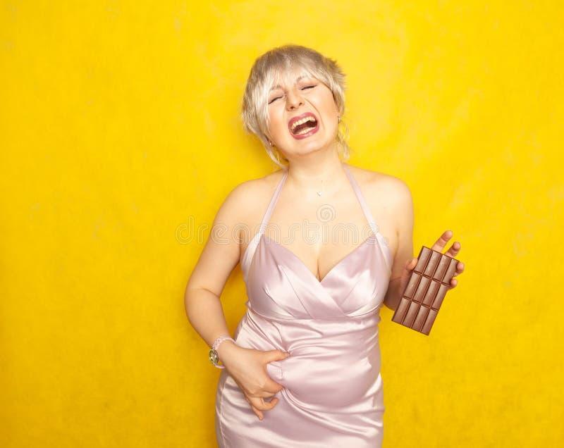La donna grassottella sta con un fronte infelice e una barra di cioccolato in sua mano e tocca il grasso sulla sua pancia paffuta fotografie stock