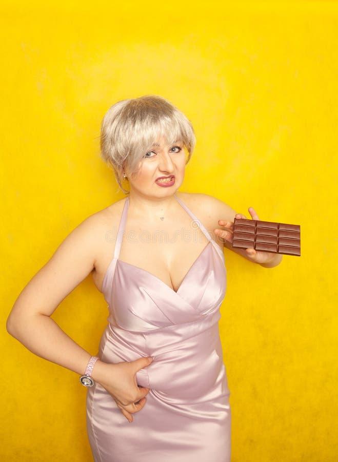 La donna grassottella sta con un fronte infelice e una barra di cioccolato in sua mano e tocca il grasso sulla sua pancia paffuta immagini stock
