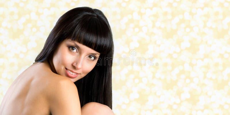 La donna graziosa con capelli neri diritti lunghi che esaminano la macchina fotografica, è fotografie stock libere da diritti