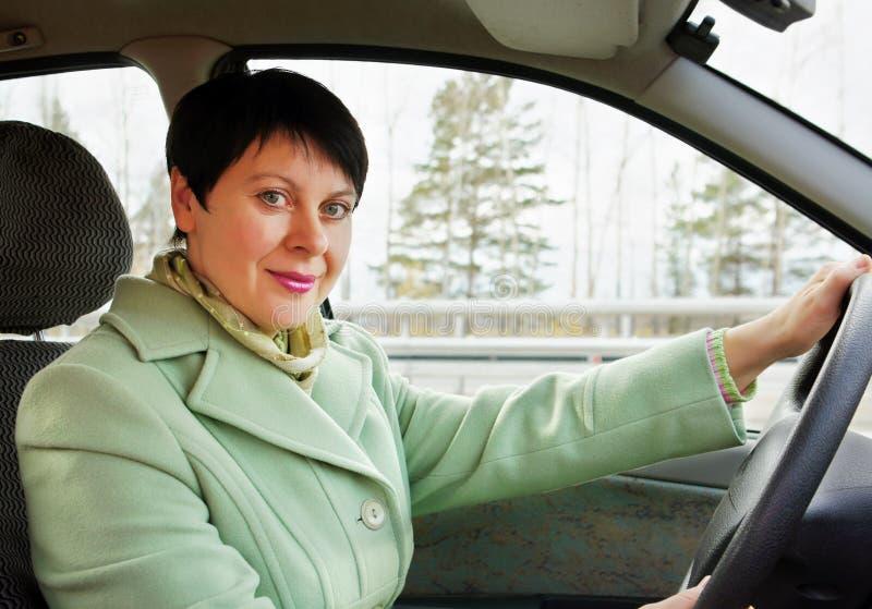La donna graziosa conduce un'automobile fotografie stock
