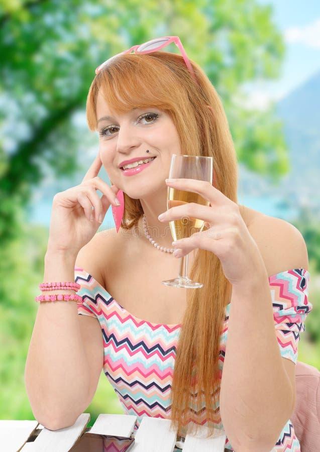 La donna graziosa della testarossa beve un bicchiere di vino, pianta su backgr immagini stock libere da diritti