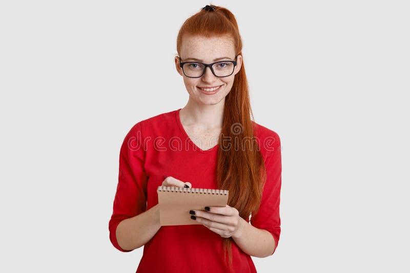 La donna graziosa dello zenzero Freckled con la coda di cavallino, annota delicatamente in blocco note con la penna, le informazi fotografie stock
