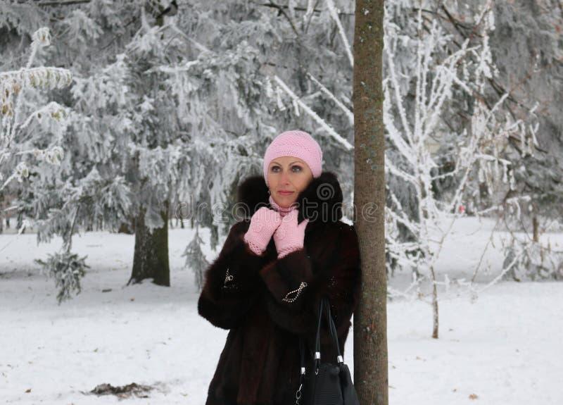 La donna graziosa e ricca in pelliccia sta posando vicino all'albero fotografia stock libera da diritti