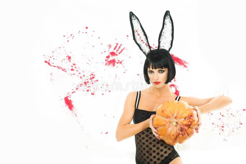La donna graziosa ha coperto del coniglio del vestito con le zucche Ragazza sexy dello zombie che tiene una zucca su fondo sangui immagini stock libere da diritti