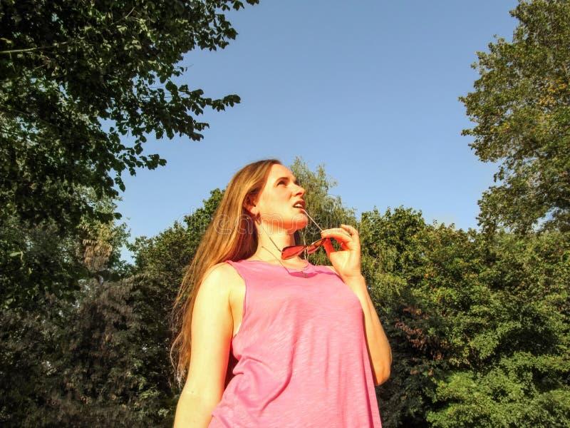 La donna graziosa morde sul suo ricevitore telefonico degli occhiali da sole e cerca contro lo sfondo degli alberi e del cielo bl immagini stock libere da diritti